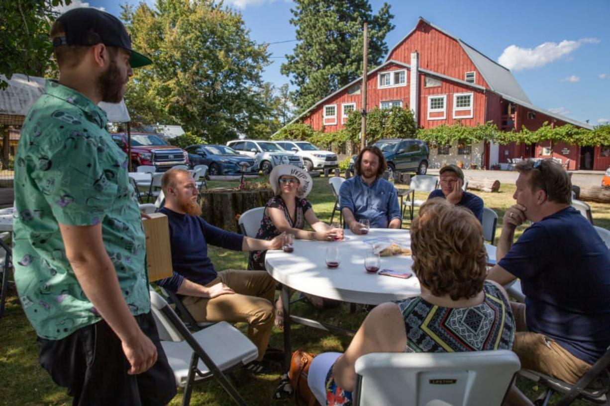 English Estate Winery tasting room manager Andrew Starr, left, talks to a group of visitors from Wisconsin on Sunday, day two of a three-day Southwest Washington Winery Association Labor Day Weekend Wine Tour. English Estate is among 16 participating wineries in Clark County. (Elayna Yussen for The Columbian)