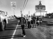 Randy Williams waves a strike sign at a passing truck outside a grocery store on Fourth Plain Boulevard and 109th Avenue in December 1980. Williams was participating in a retail workers strike.