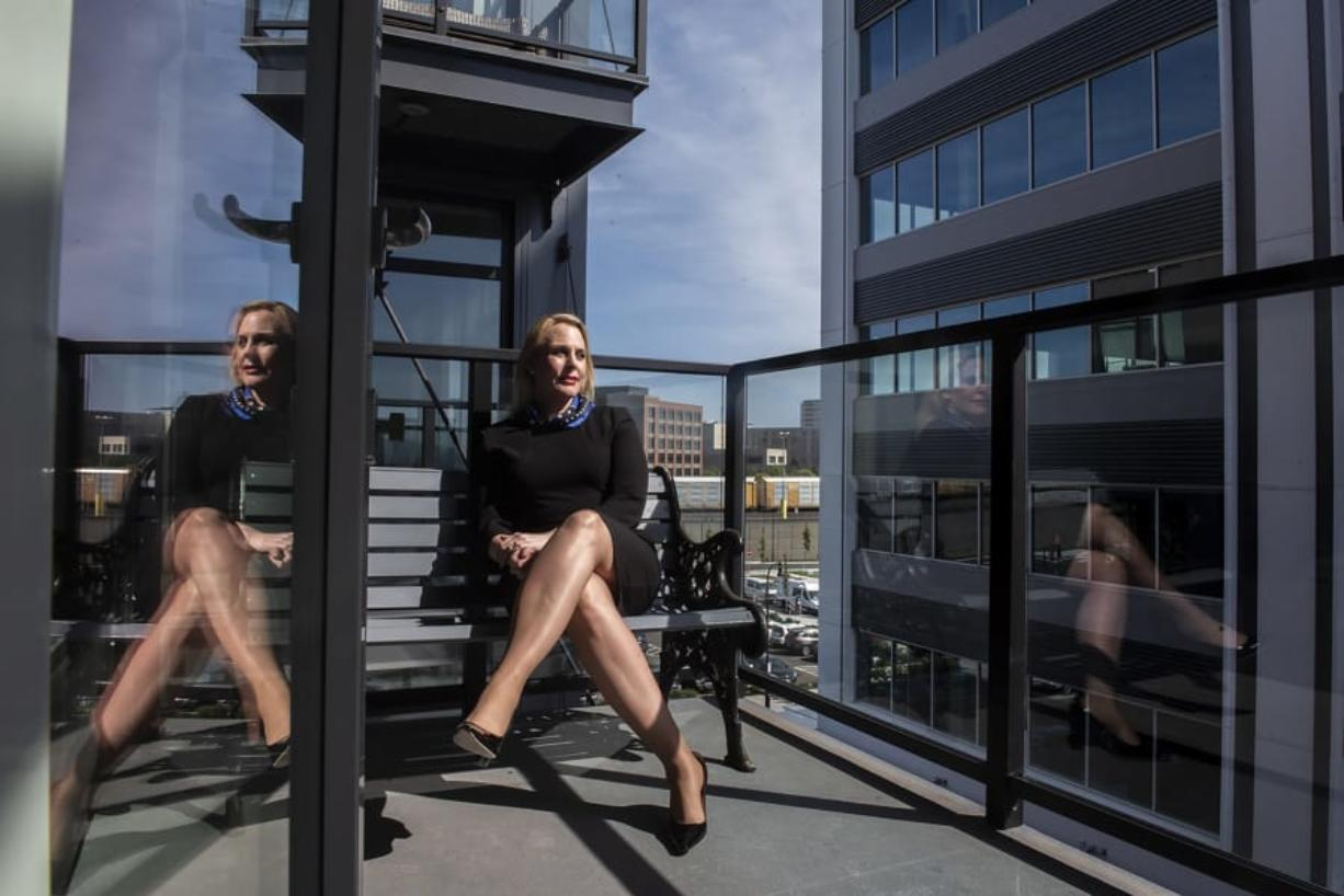 Kimberly Thornbury sits on a balcony at The Rediviva on Wednesday. She relocated from New York City and works in the building next door.