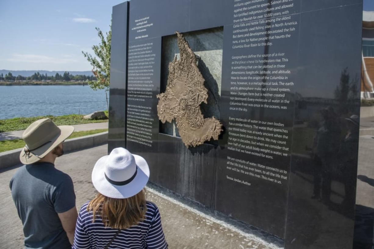 Tom Pearson, left, and Kathryn Pearson of Vancouver examine the Columbia River water feature at The Waterfront Vancouver last week. Water deposits can be seen staining the bottom of the granite and copper monolith after a month of public use.