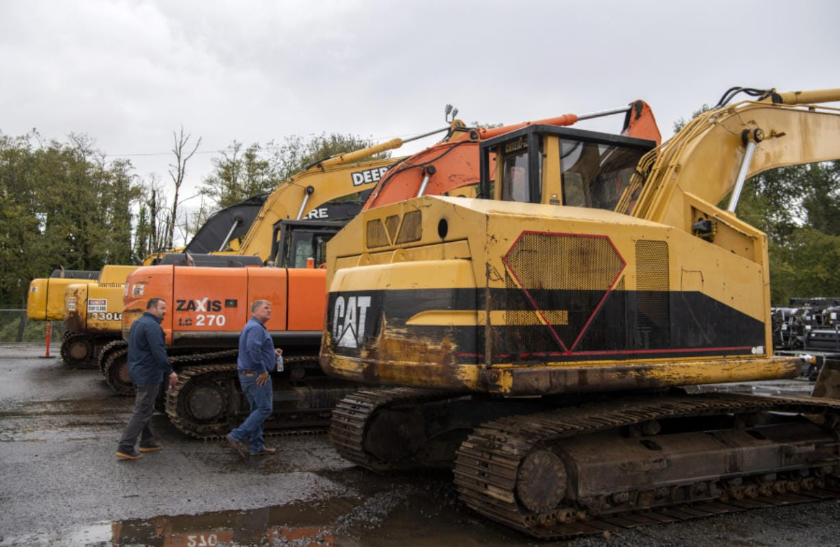 Robertson & Olson fleet manager Darin Borg, left, and owner Matt Olson, right, look at a row of excavators at the new J. Stout Auctions facility in Washougal on Tuesday. Alisha Jucevic/The Columbian