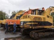 Robertson & Olson fleet manager Darin Borg, left, and owner Matt Olson, right, look at a row of excavators at the new J. Stout Auctions facility in Washougal on Tuesday.