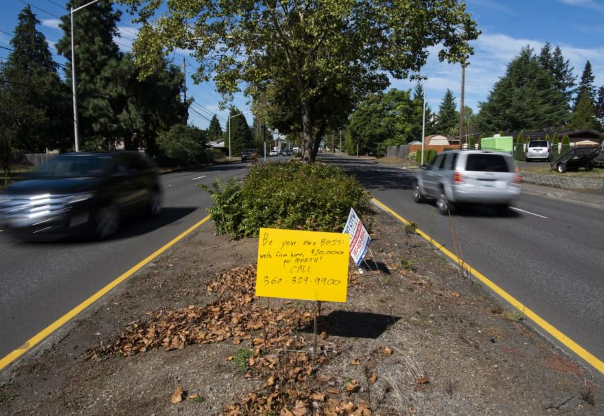 A hand-scrawled sign promising people $20,000 per month for working at home stands in the median along Mill Plain Boulevard near PeaceHealth Southwest Medical Center in Vancouver.