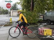 Sally Butts of the Vancouver Bicycle Club checks her left for oncoming traffic before leaving Bike Clark County to pick up leftover produce from the Vancouver Farmers Market on Sunday.