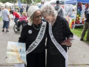 "Peace and Justice hero re-enactors Lydia Folwer Newcomb, left, and Sonya Norton share a moment during the 16th annual Peace and Justice Fair at Esther Short Park on Saturday. ""Re-enactors are supposed to know about the person they represent,"" Norton said. ""I actually read up on Eleanor Roosevelt so I can inform visitors."