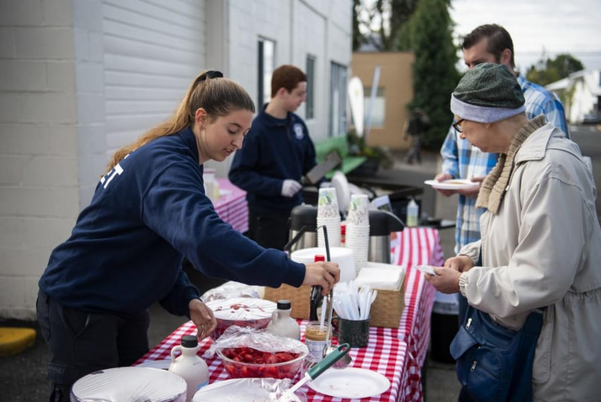 Clark County Fire Department cadet Danielle Haner, left, helps Deann Blakeman during a Superpower Pancake Feed at North County Community Food Bank Thursday. The food bank was the top fundraiser at this year's Give More 24.