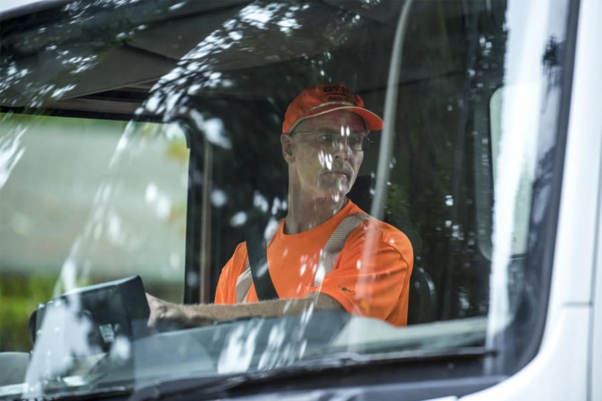 Bill Lamkin, a maintenance worker with Vancouver Public Works, checks his mirrors while driving a vacuum intake street sweeper through the DuBois Park neighborhood. Lamkin has worked for the city for the department for 12 years, rotating on and off sweeping jobs to other maintenance tasks.