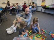 Ava West, 2, of Battle Ground, from left, joins her grandfather, Bill Jackson, and classmate Emma Betka, 3, as they play with blocks Wednesday afternoon at Daybreak Primary School. The activity was part of Let's Play and Learn Together, a free weekly drop-in program hosted by Battle Ground Public Schools for students age 5 or younger.