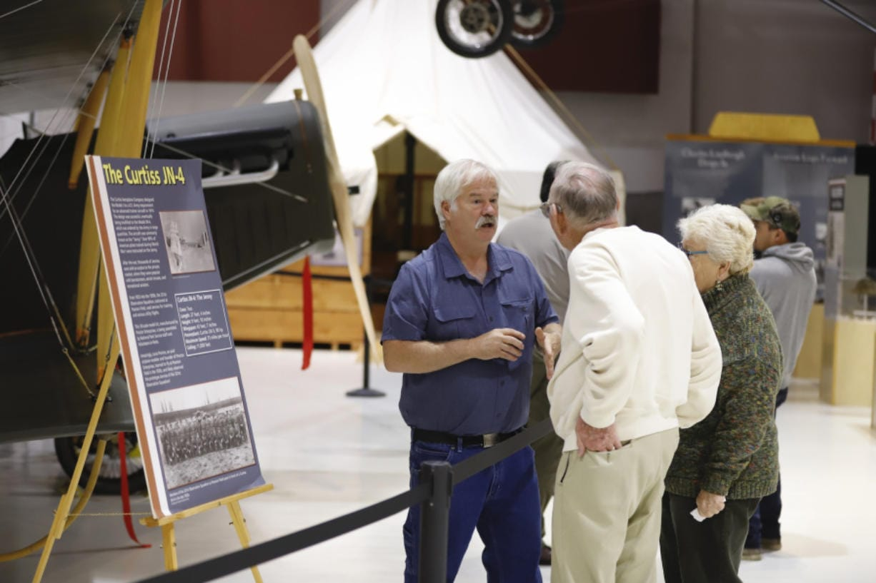 """Mark Smith, left, of Century Aviation discusses the A 1918 Curtiss JN-4 """"Jenny""""  airplane that was dedicated as part of the exhibit at Pearson Air Museum on Saturday."""