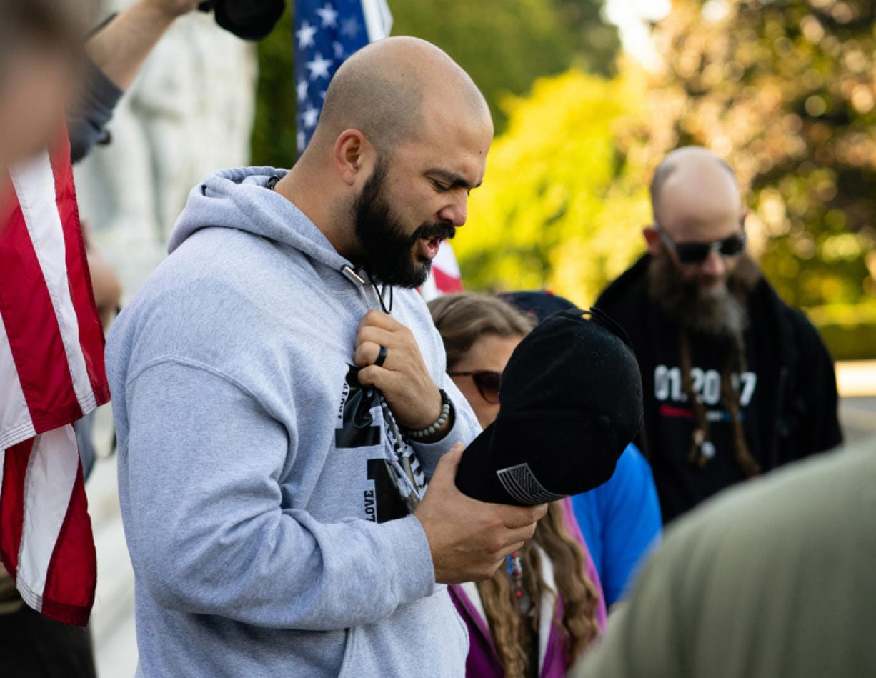 Joey Gibson, leads supporters in prayer on the steps of the Capitol Building in Salem, Ore. following the conclusion of a flag waving rally in October 2017. Gibson, the leader of Patriot Prayer, is extremely active on social media, where he has attracted a large following.