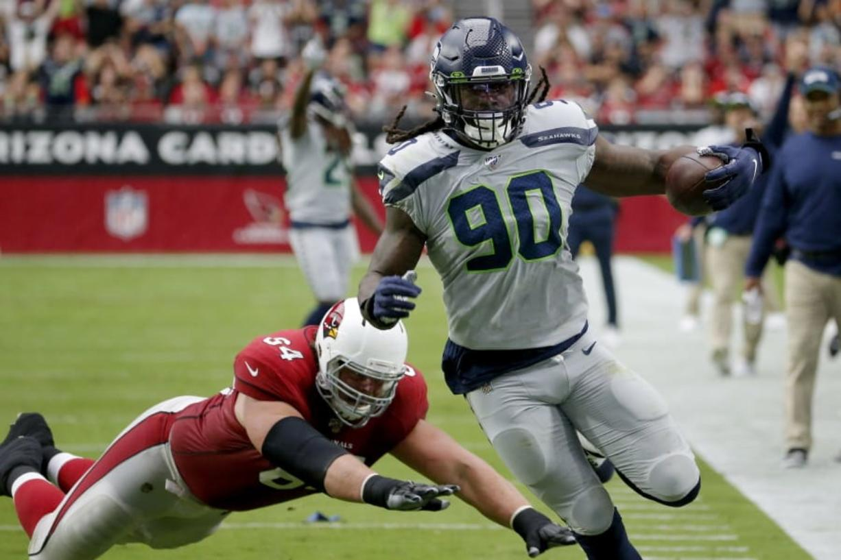 Seattle Seahawks outside linebacker Jadeveon Clowney (90) runs back an interception for a touchdown as Arizona Cardinals offensive guard J.R. Sweezy (64) defends during the first half of an NFL football game, Sunday, Sept. 29, 2019, in Glendale, Ariz.
