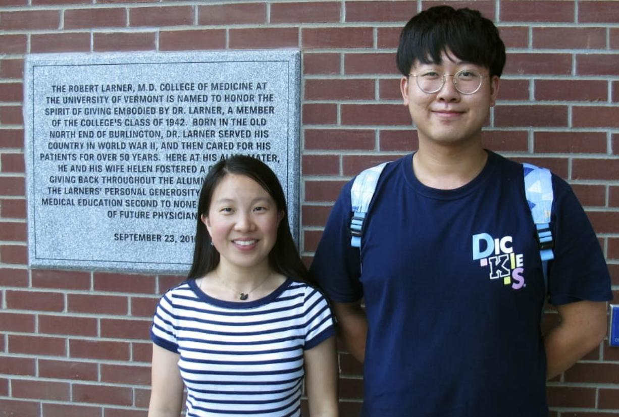 In this photo Aug. 16, 2019, photo, Chinese graduate students Zhaojin Li, left, and Pengfei Liu, pose in front of the entrance to the Robert Larner College of Medicine at the University of Vermont in Burlington, Vt. Some higher education officials are concerned by a drop in the number of international students coming to the United States, especially from China. Li and Liu say that some of their relatives were concerned for their safety in coming to the United States, but they are too busy with their studies to focus on geopolitical issues. (AP Photo/Wilson Ring)