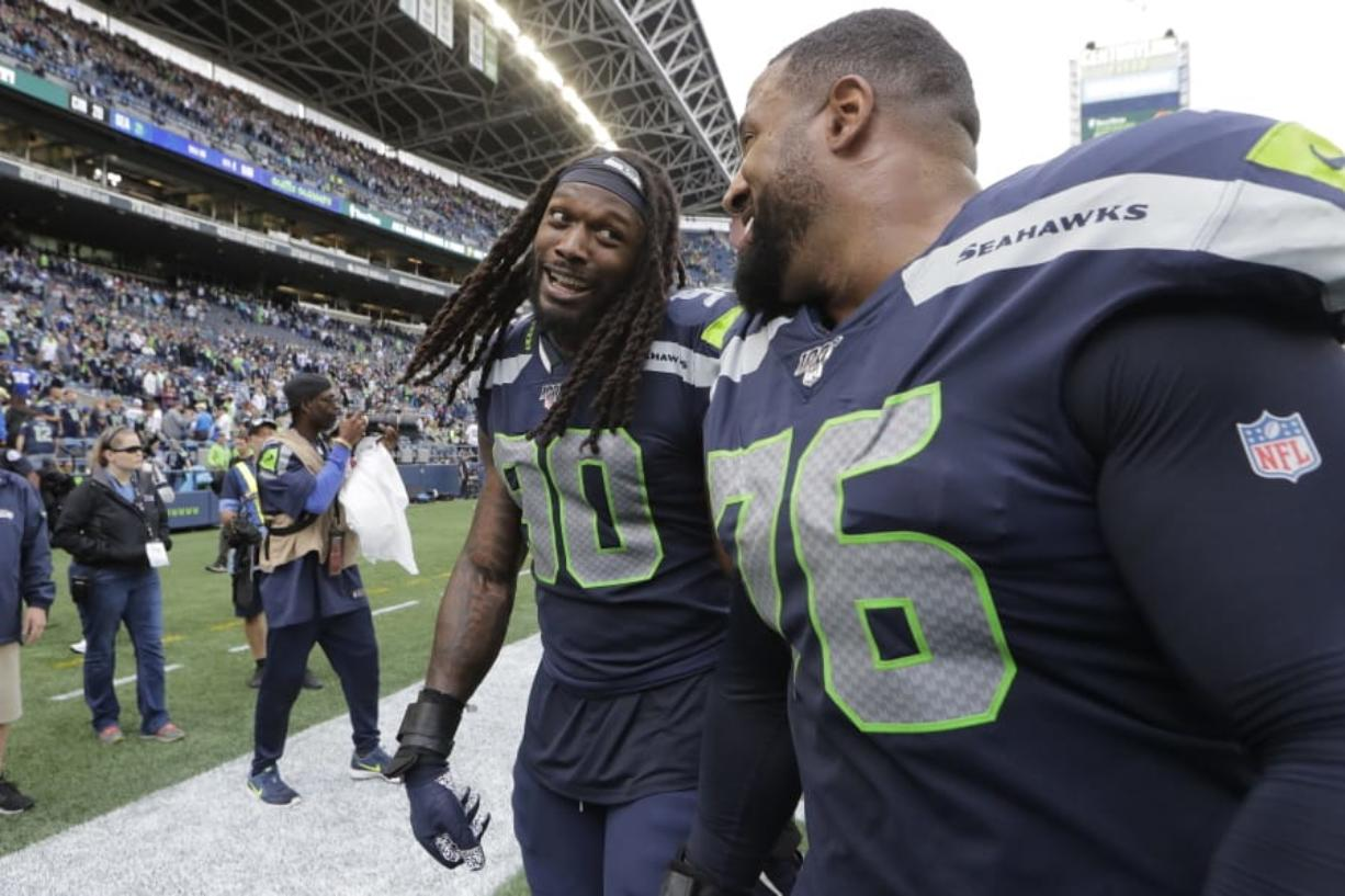 Seattle Seahawks defensive end Jadeveon Clowney, left, talks with teammate Duane Brown, right, after they defeated the Cincinnati Bengals in an NFL football game, Sunday, Sept. 8, 2019, in Seattle.