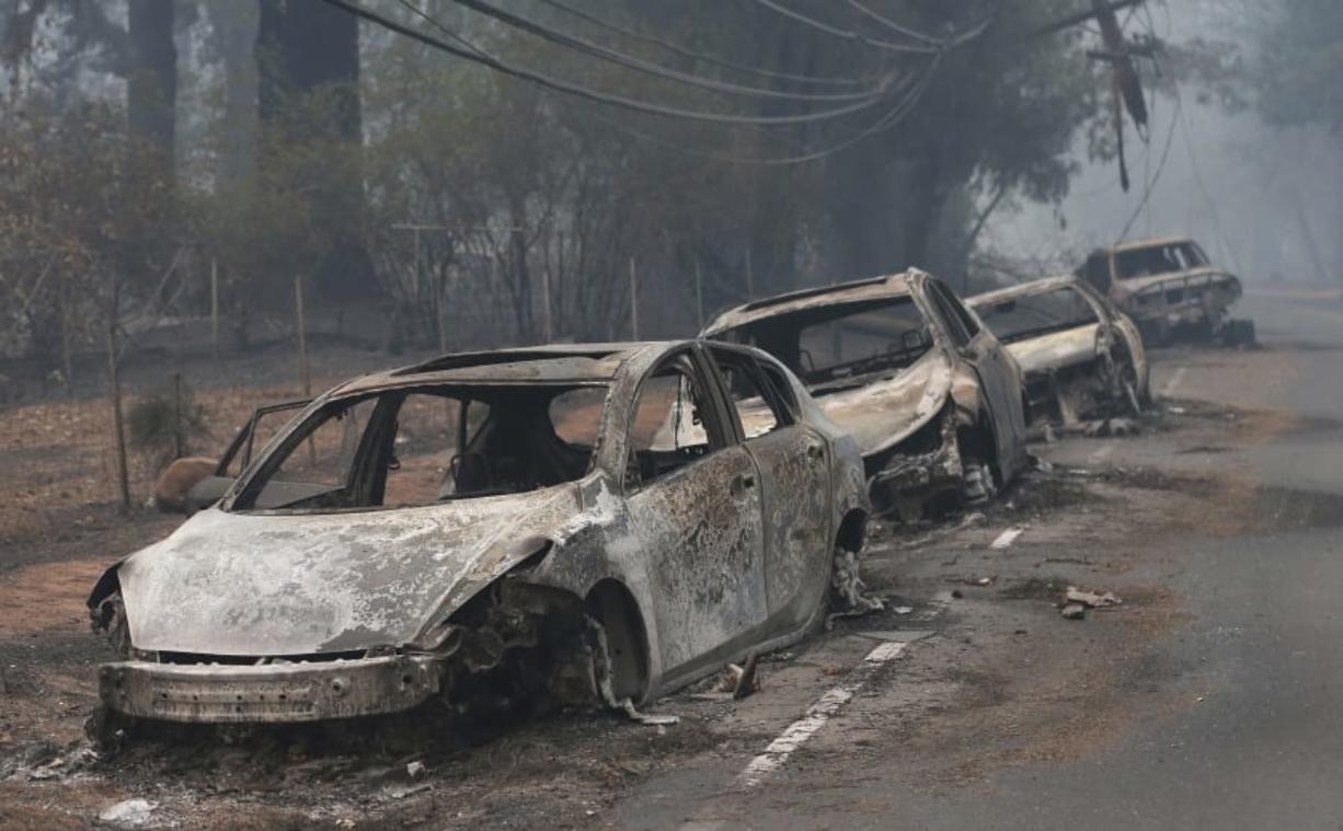 FILE - This Nov. 9, 2018, file photo the burned out hulks of cars abandoned by their drivers sit along a road in Paradise, Calif. In July 2019, the legislature approved and Gov. Gavin Newsom signed a law that requires the state's three investor-owned utilities to spend a combined $5 billion on safety improvements and adopt new safety standards.
