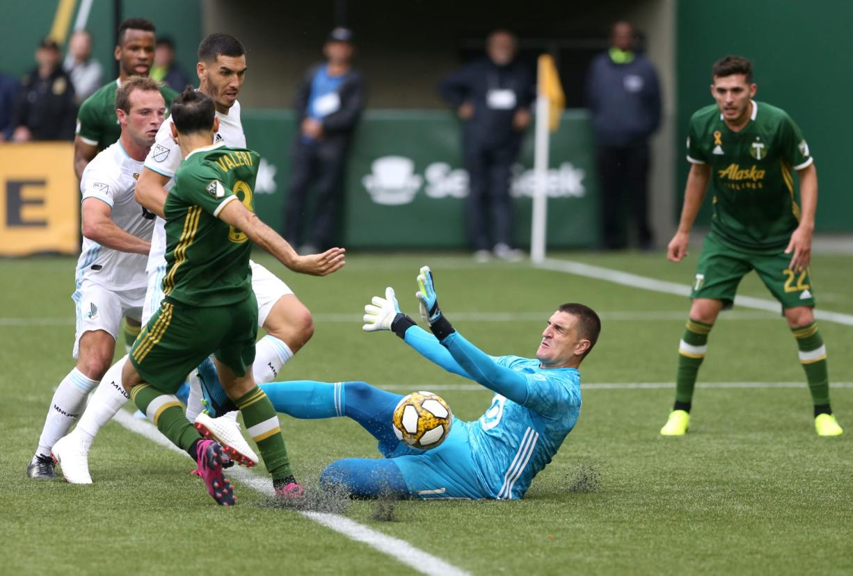 Minnesota United FC goalkeeper Vito Mannone (1) makes a save against Portland Timbers'  Diego Valeri (7) during an MLS soccer match at Providence Park, Sunday, Sept. 22, 2019, in Portland, Ore. (Sean Meagher/The Oregonian via AP)