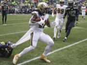 Seattle Seahawks' Shaquill Griffin, left, grabs hold of a piece of uniform as he tries to stop New Orleans Saints' Alvin Kamara on a run during the second half of an NFL football game Sunday, Sept. 22, 2019, in Seattle.