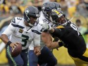 Seattle Seahawks quarterback Russell Wilson (3) scrambles past Pittsburgh Steelers defensive end Cameron Heyward (97), who is blocked by Seahawks offensive guard Ethan Pocic (77) during the second half of an NFL football game in Pittsburgh, Sunday, Sept. 15, 2019. The Seahawks won 28-26. (AP Photo/Gene J.