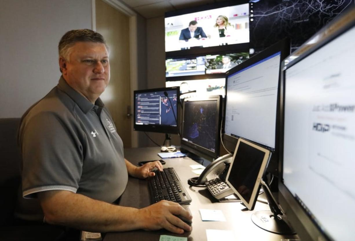In this July 30, 2019, photo, Paul Hildreth, emergency operations coordinator for the Fulton County School District, works in the emergency operations center at the Fulton County School District Administration Center in Atlanta. Artificial Intelligence is transforming surveillance cameras from passive sentries into active observers that can immediately spot a gunman, alert retailers when someone is shoplifting and help police quickly find suspects. Schools, such as the Fulton County School District, are among the most enthusiastic adopters of the technology. (AP Photo/Cody Jackson)