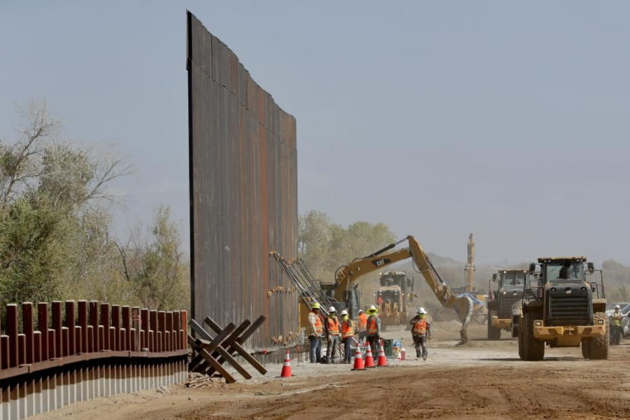 Government contractors erect a section of Pentagon-funded border wall Tuesday along the Colorado River in Yuma, Ariz. The 30-foot high wall replaces a five-mile section of Normandy barrier and post-n-beam fencing, shown at left, along the border that separates Mexico and the United States. (Matt York/Associated Press)