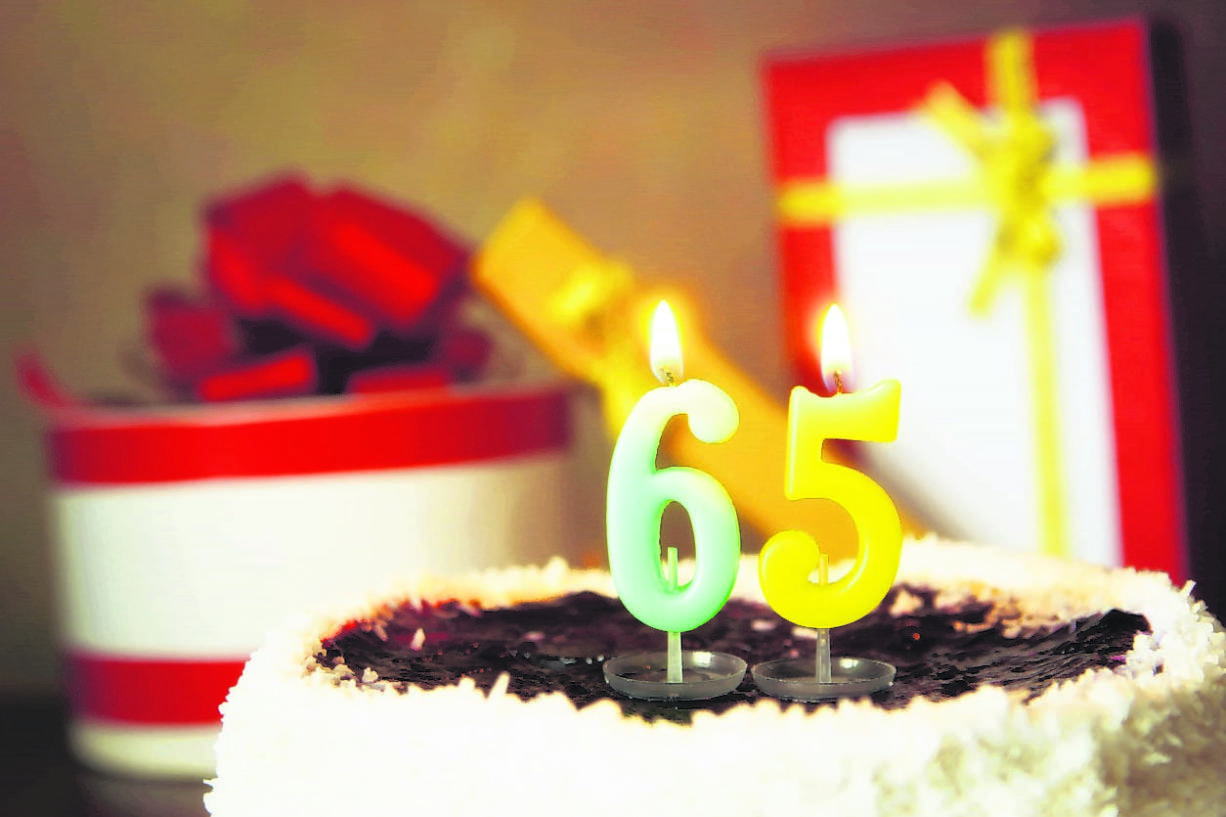 Sixty five years birthday. Cake with burning candles and gifts
