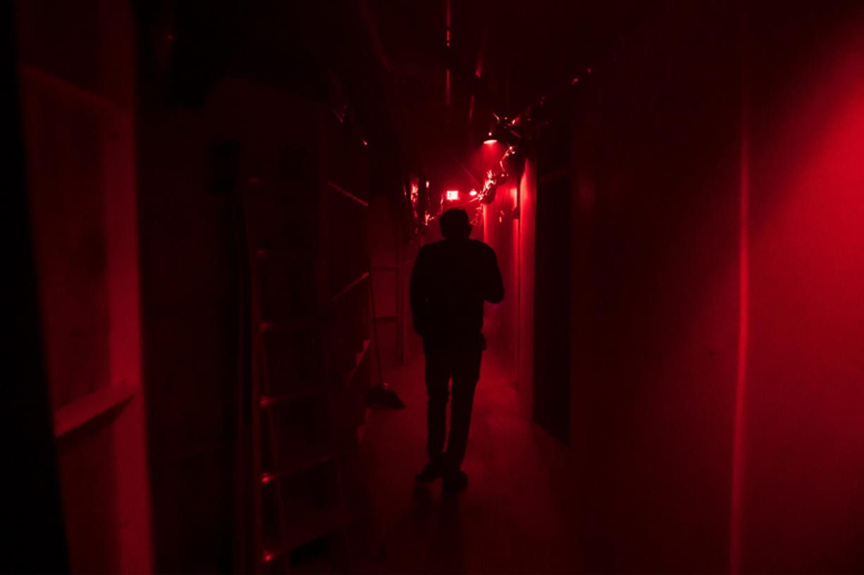 Jason Greeley-Roberts, an owner of the Clark County Scaregrounds, walks through an access corridor behind one of his haunts while checking on the actors in 2018. Scaregrounds takes place at Clark County Fairgrounds through Halloween.