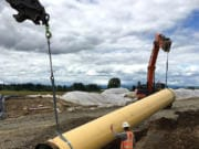 Workers lower a pipe into a trench as part of Oregon's Willamette Water Supply Program, which will add a new water filtration plant and more than 30 miles of pipeline to accommodate future population growth in the Hillsboro and Tualatin Valley Water District area.