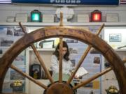 "Isabel Alanis, 12, takes notes on the historic steering wheel from a Columbia River ferry during an Odyssey Middle School class visit to the Clark County Historical Museum's new ""Currents of Progress"" exhibit."
