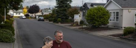 Cheryl and Ken Lickar pose for a photo near their home in Cascade Parks Estates, a 55-and-older manufactured home community where monthly rent is increasing $125 on Jan. 1. (Nathan Howard/The Columbian)