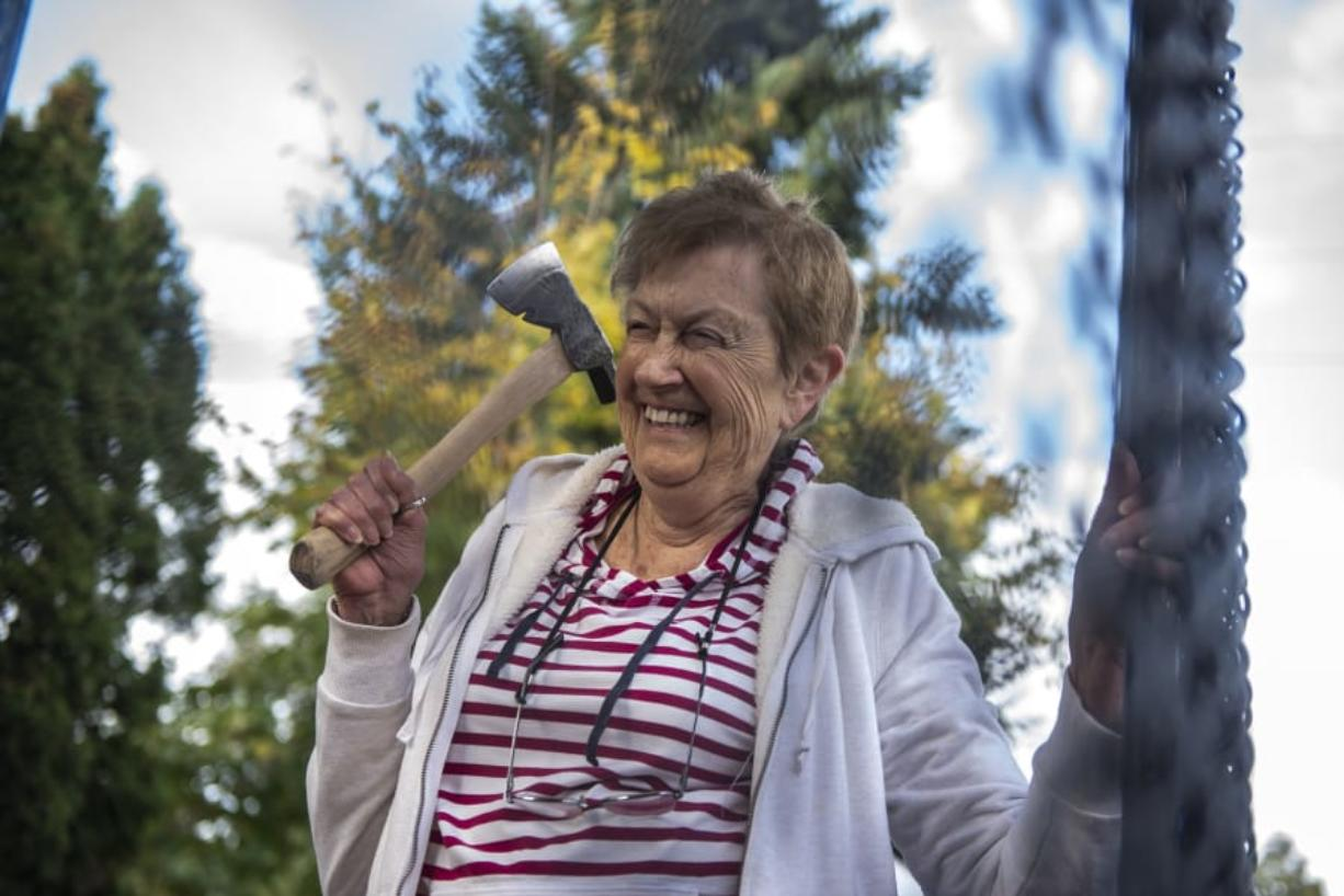 Jo Borwick, 84, laughs while taking aim during an ax throwing event at Highgate Senior Living. Many of the seniors held onto the walls of the mobile ax throwing unit for balance as they threw.