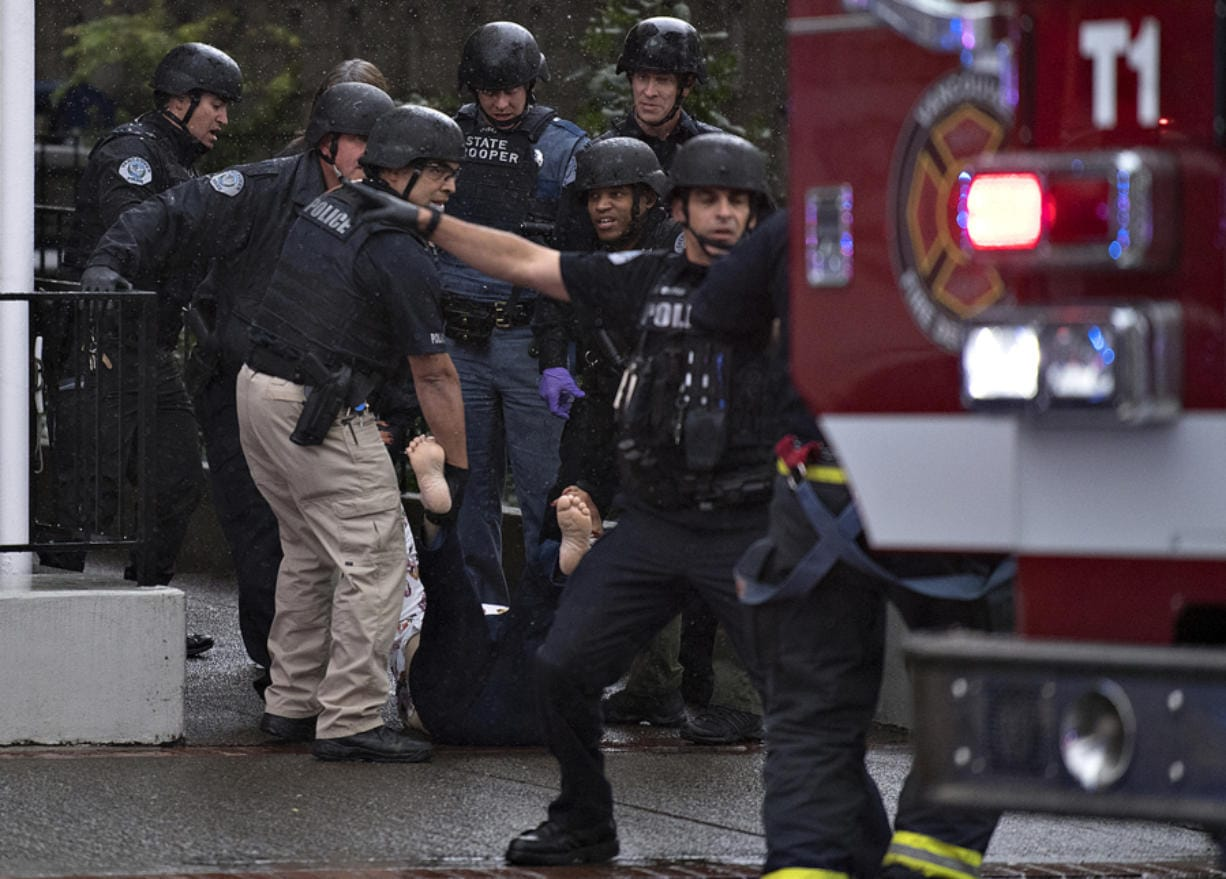 Police carry a wounded woman to safety after a shooting at Smith Tower Apartments on Oct. 3.