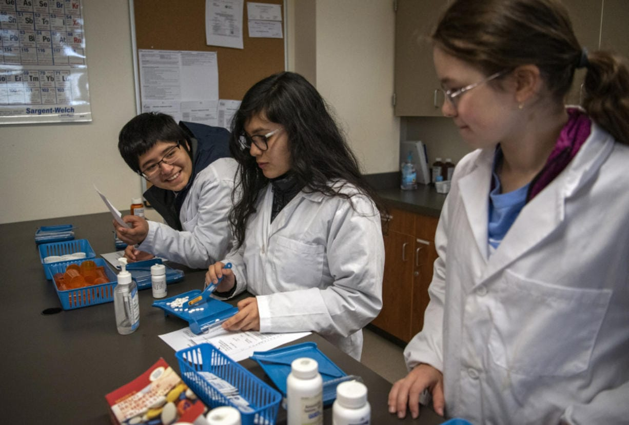 Henrietta Lacks Health and Bioscience High School seniors Dante Diaz, from left, Paola Terrazas and Anastasiya Kashyrna demonstrate how they learn how to count medication in their pharmacology classroom. The classrooms use pretend medicine, like cornstarch pills, or even beans and beads to mimic medication. Henrietta Lacks High offers programs in biotechnology, biomedical engineering, public health, pharmacy, nursing and patient services.
