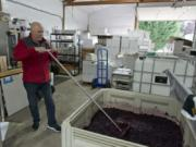 Don Klase mixes wine in a vineyard at Dolio Winery in Battle Ground.