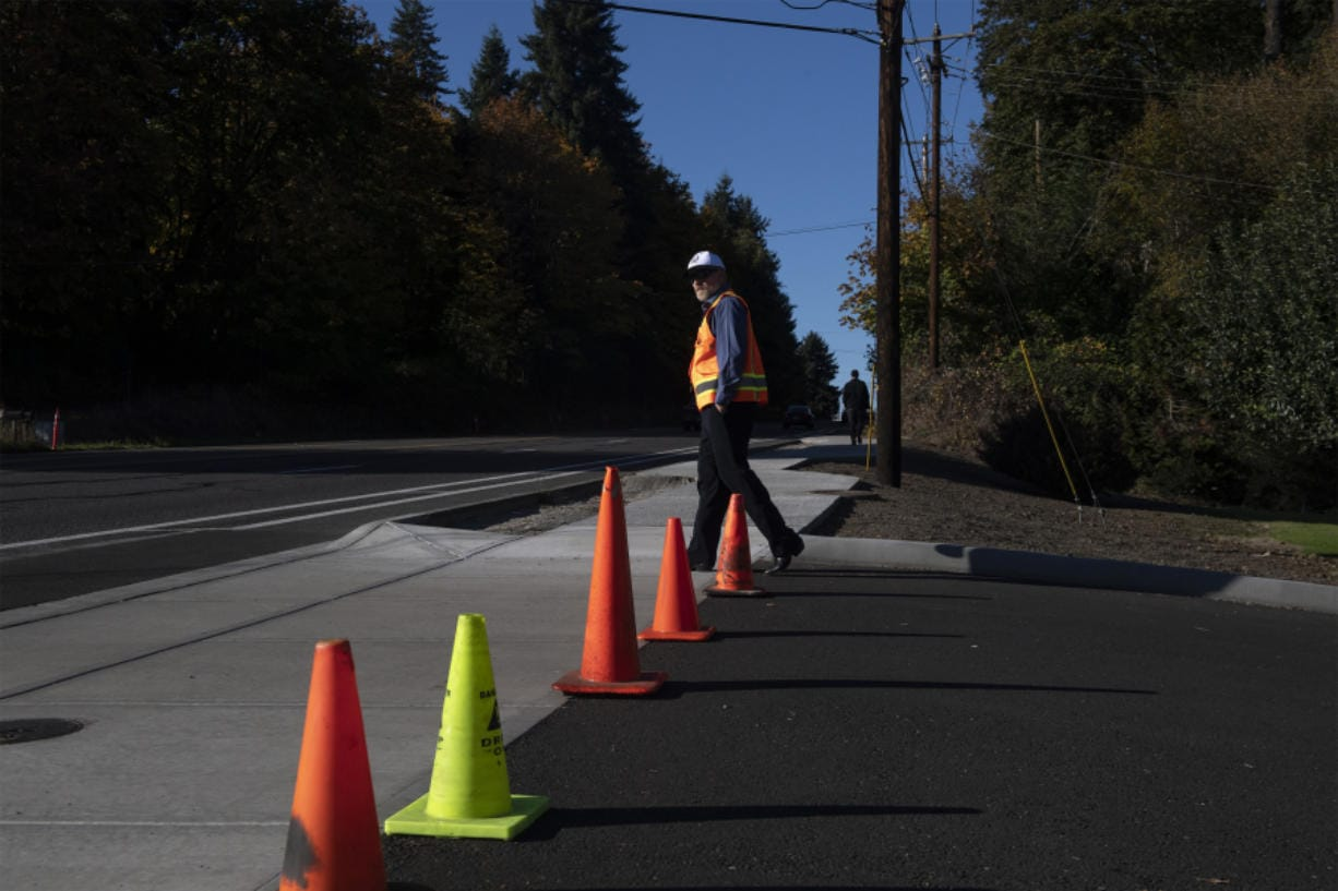 Les MacDonald, the incoming deputy public works director for Clark County, examines a section of new sidewalk along the east side of Highway 99 following a short sidewalk celebration event Thursday afternoon.