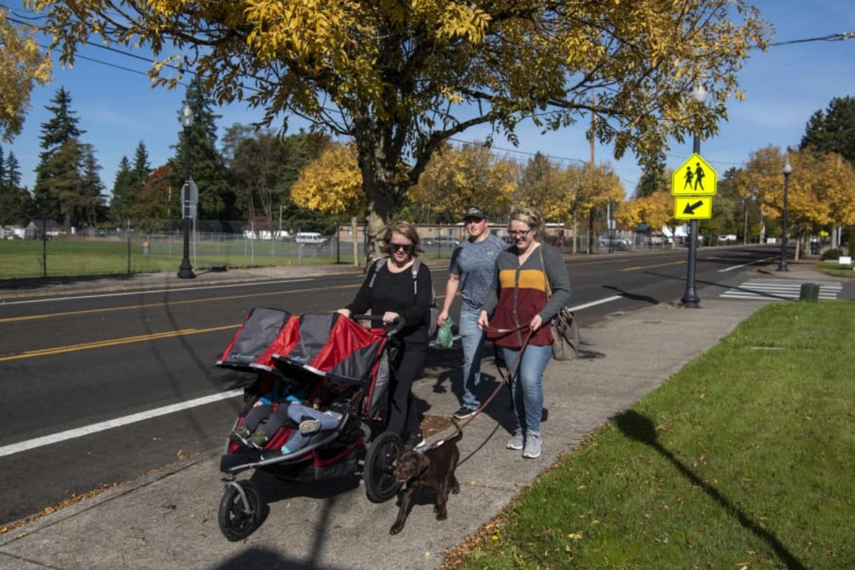 Emily Gillingham, from left, of La Center, and Mitchell Stivers and Alexis Gillingham, both of Battle Ground, take an afternoon stroll together with Gillingham's kids and Stivers and Alexis Gillingham's new puppy along North Parkway Avenue in Battle Ground on Friday.