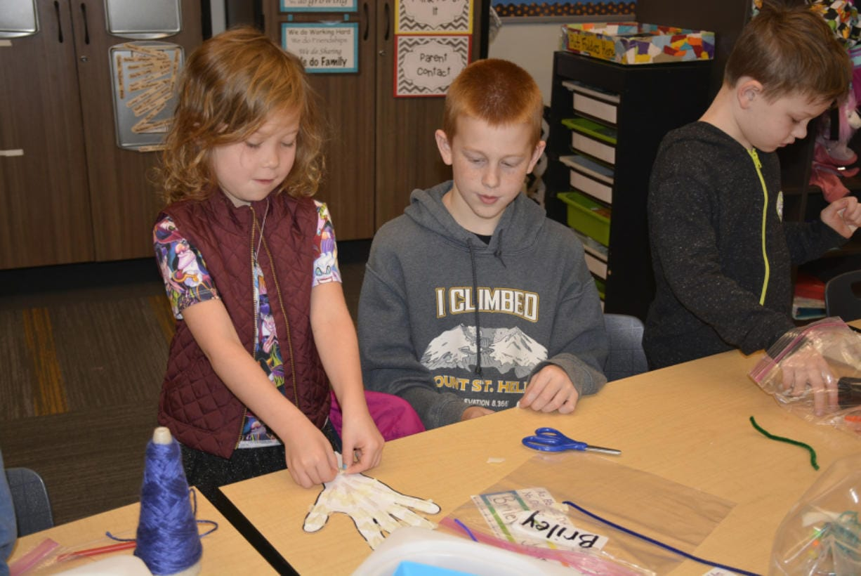Briley Johnson and Jacob Sanders work together to construct a moving hand.
