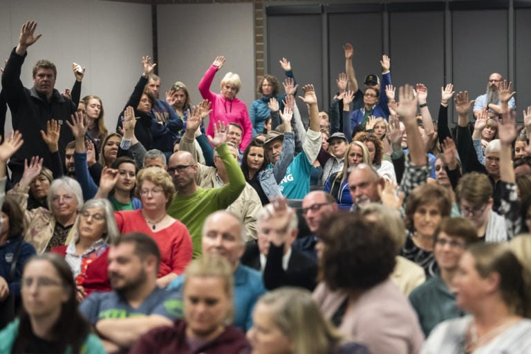 Attendees raise their hands to show their opposition to new sex education curriculum during a Battle Ground Public Schools Board of Directors meeting on Monday night, Oct. 14, 2019. (Nathan Howard/The Columbian)