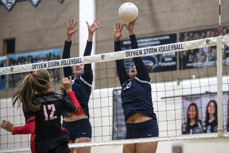 Skyview's Allyson Reid and Tyra Schaub touch the ball over the net during a game against Camas at Skyview High School on Tuesday night, Oct. 15, 2019. (Nathan Howard/The Columbian)