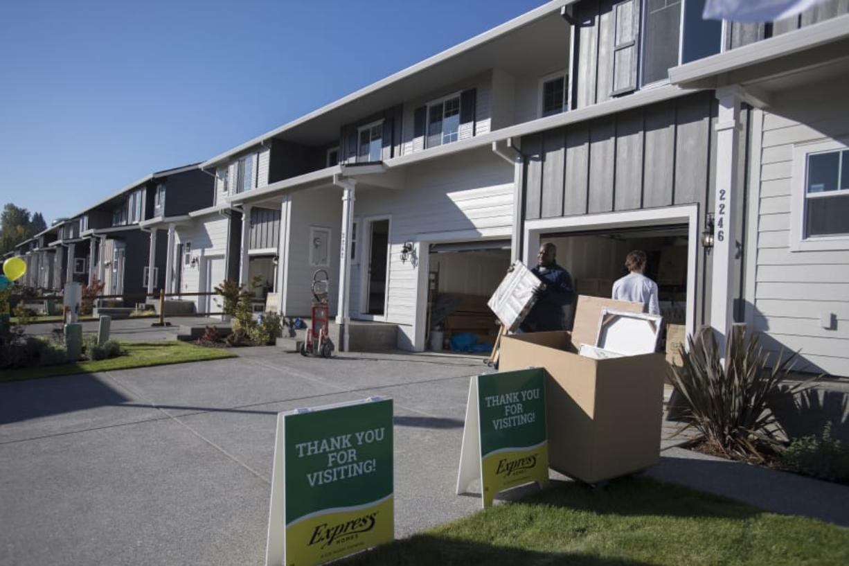 Wendell Wilson of Budget Movers helps move items into a four-plex at the Four Seasons development Thursday morning. The ongoing project from Ginn Development contributed to a spike in the number of single-family building permits issued by the city of Vancouver last month. (Photos by Amanda Cowan/The Columbian)