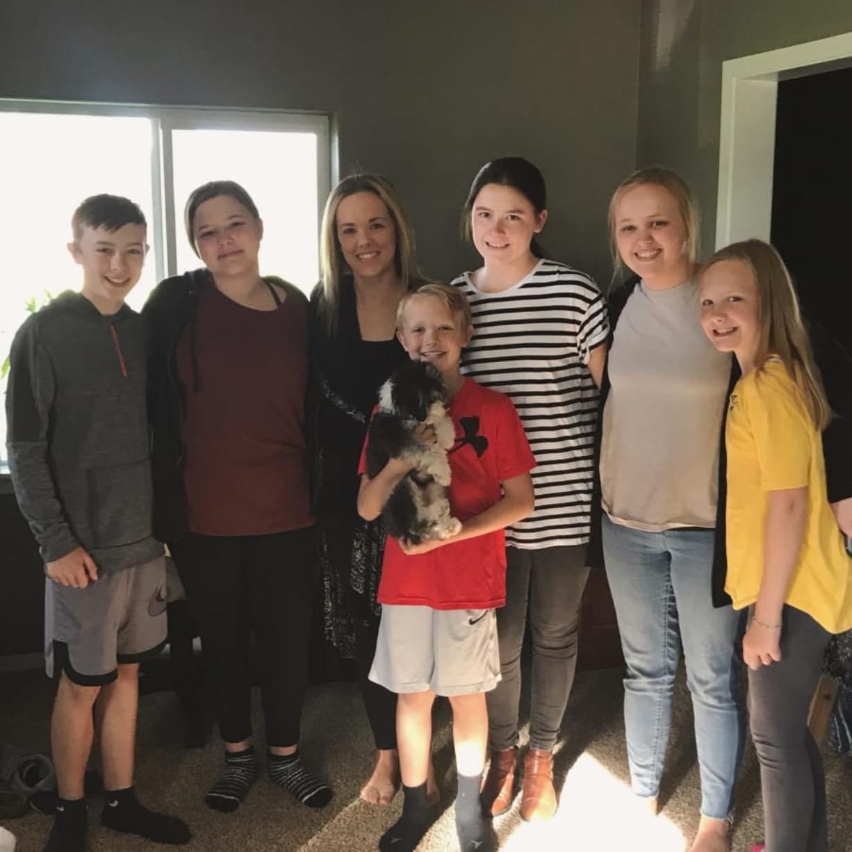 Ashley Eggleston, center, credits her three kids and three teenagers with saving her life after her heart stopped earlier this month. The teens called 911, started CPR and comforted her kids while first responders worked on her. From left: Owen Meyer, Emilee Tikka, Eggleston, Evan Meyer, Kate Nylund, Eva Sarkinin and Nora Meyer.