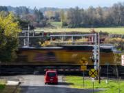 A car waits for a freight train to pass on Mill Street near McCuddy's Ridgefield Marina on Wednesday.