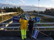 Lehman Holder, left, and Sharon Fujioka, both with the Sierra Club, campaign for various Vancouver candidates Friday on the Interstate 205 overpass on Northeast Ninth Street in Vancouver.