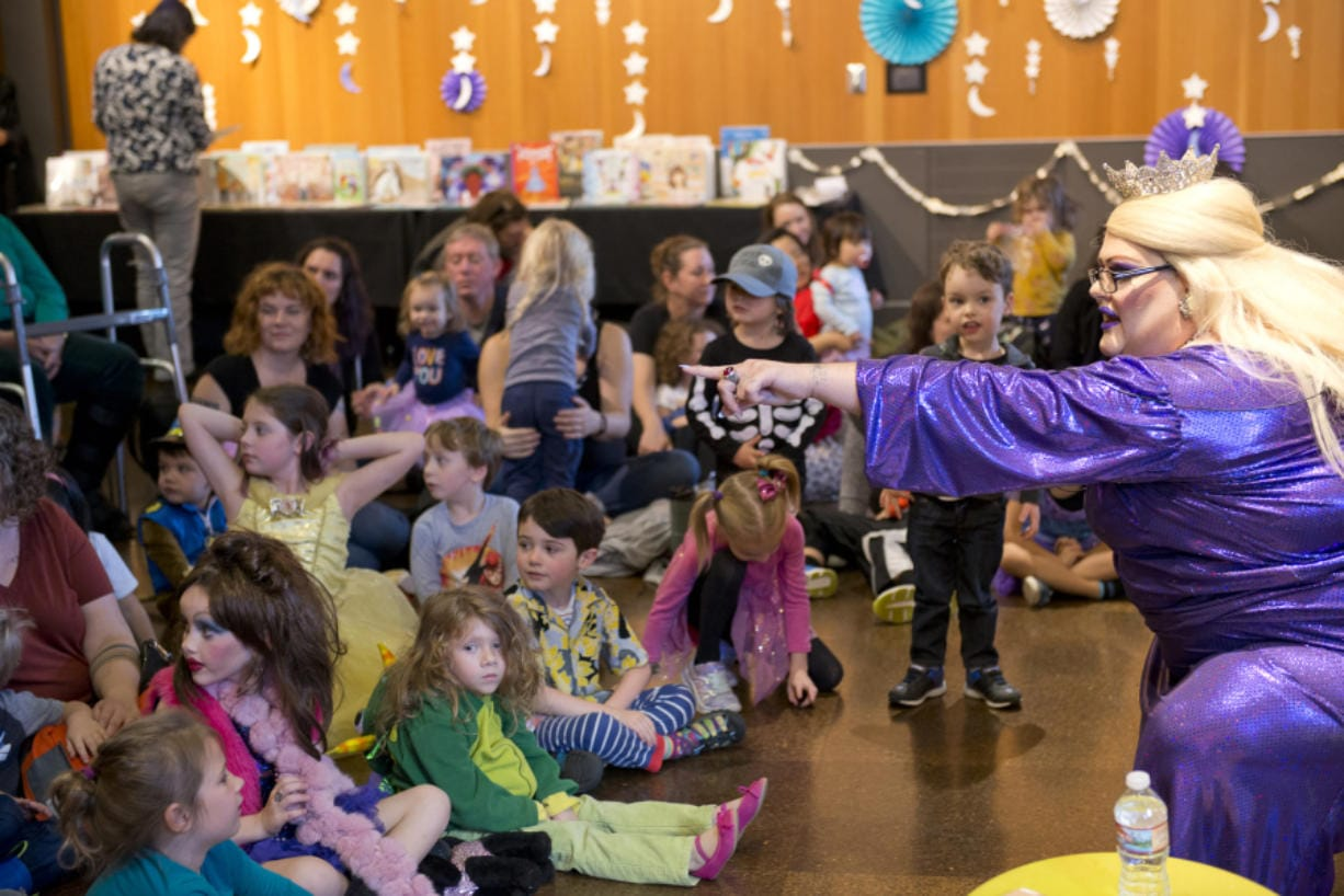 Drag queen Tree Empress 45 Onalicious Mercury asks kids what they want to be when they grow up Sunday at the Drag Queen Story Hour at the Vancouver Community Library. More than 100 children and parents attended the event to sing, dance and listen to storybooks. (James Rexroad for The Columbian)