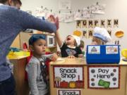 Thomas Duncan encourages his students, from left, Austin Park, 3,  Addison Horn, 3, and Rylie Allen, 3, to keep playing while a tour observes the class in district's new the Early Learning Center. To keep up with rapid growth, the school board plans to ask voters to approve a facilities bond next February.
