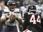 Seattle Seahawks quarterback Russell Wilson (3) works in the pocket as Atlanta Falcons defensive end Vic Beasley (44) pressures during the first half of an NFL football game, Sunday, Oct. 27, 2019, in Atlanta.