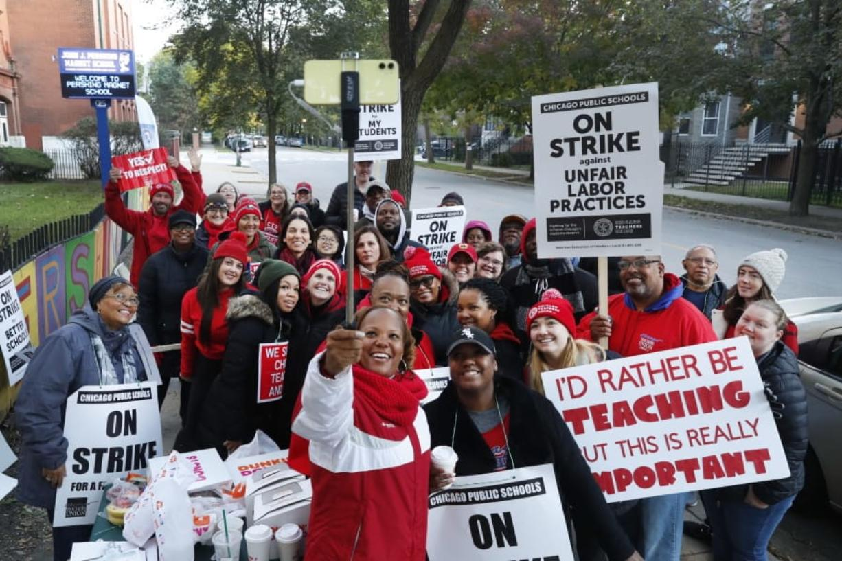 Striking teachers and support staff pose for a group shot outside the John J. Pershing Magnet School on the first day of their strike in the city's Bronzeville neighborhood Thursday, Oct. 17, 2019, in Chicago. Chicago teachers went on strike Thursday, marching on picket lines after failing to reach a contract deal with the nation's third-largest school district in a dispute that canceled classes for more than 300,000 students. (AP Photo/Charles Rex Arbogast)