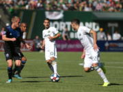 Portland Timbers' Sebastian Blanco, center, passes the ball ahead to Christhian Paredes, right, as San Jose Earthquakes' Jackson Yueill, front left, defends during an MLS soccer match in Portland, Ore., Sunday, Oct. 6, 2019.