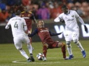 Portland Timbers defender Jorge Villafana (4) pressures Real Salt Lake midfielder Everton Luiz (25) with help from forward Dairon Asprilla (27) aduring the first half of an MLS soccer Western Conference first-round playoff match in Sandy, Utah, Saturday, Oct. 19, 2019.