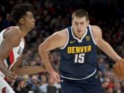Denver Nuggets center Nikola Jokic dribbles past Portland Trail Blazers center Hassan Whiteside during the first half of an NBA basketball game in Portland, Ore., Wednesday, Oct. 23, 2019.
