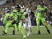 Seattle Seahawks quarterback Russell Wilson (3) scrambles before making a short pass to running back Chris Carson for a touchdown against the Los Angeles Rams during the second half of an NFL football game Thursday, Oct. 3, 2019, in Seattle.