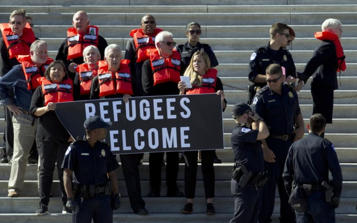 Faith leaders and members of human rights groups wear life vests symbolizing the lifesaving program are arrested by U.S. Capitol police Tuesday during a protest calling congress not to end the refugee resettlement program, at the steps of the U.S. Capitol in Washington. (Associated Press files)